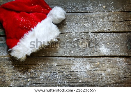 Santa Claus hat on vintage wooden boards christmas background