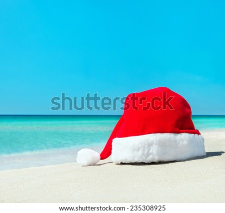 Santa Claus hat on white sand of tropical beach - Christmas or New Year's vacation concept - stock photo
