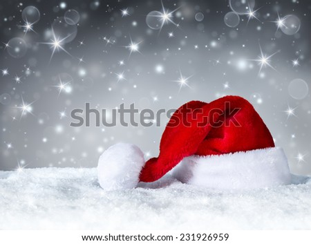 Santa Claus hat with snow and silver snowfall background  - stock photo
