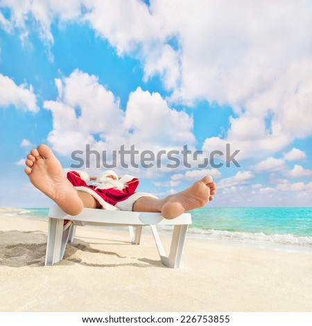 Santa Claus have a rest in chaise longue on sea beach - christmas or happy new year concept