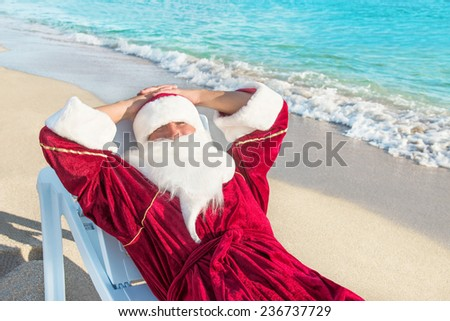 Santa Claus have a rest in lounge on sea beach - christmas or happy new year concept - stock photo