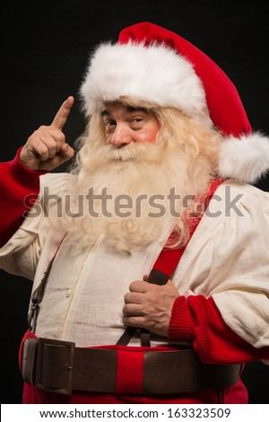 Santa Claus have an idea gesturing with finger against dark background - stock photo