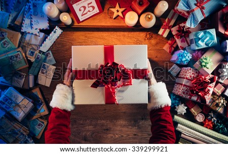 Santa Claus holding a beautiful Christmas gift box, letters and presents all around, hands top view - stock photo