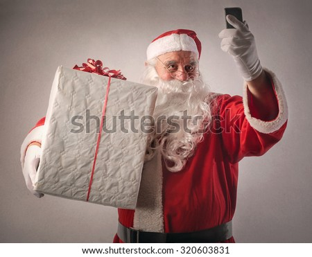 Santa Claus holding a big present and a smartphone - stock photo