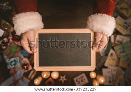 Santa Claus holding a blank blackboard hands close up, top view, desktop with gifts and Christmas letters on background - stock photo