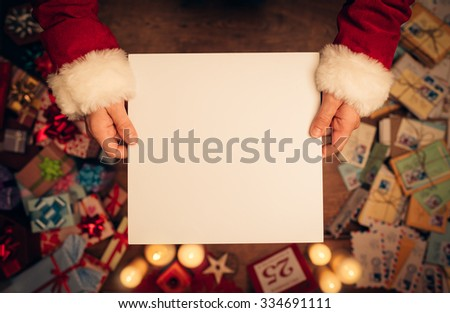Santa Claus holding a blank sign, hands close up, top view, desktop with Christmas gifts and letters on background - stock photo