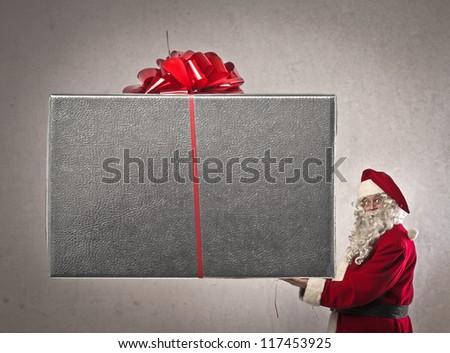 Santa Claus holding a giant present - stock photo