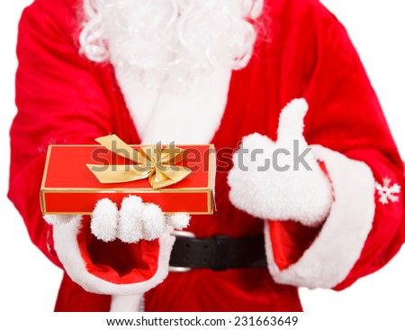 Santa Claus Holding a Gift Box with Ribbon - stock photo