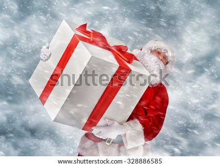 Santa Claus holding a huge Christmas gift.