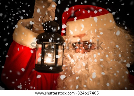 Santa Claus holding a lantern to see in the dark - stock photo