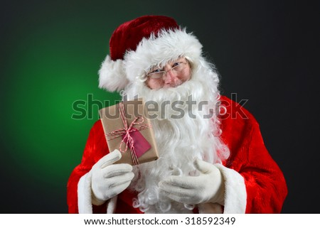 Santa Claus holding a plain brown wrapped package. The eco friendly recyclable gift is tied with string and has a blank gift tag. On a light ot dark green background.