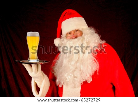 Santa Claus holding a serving tray with a large glass of beer. Horizontal format - stock photo