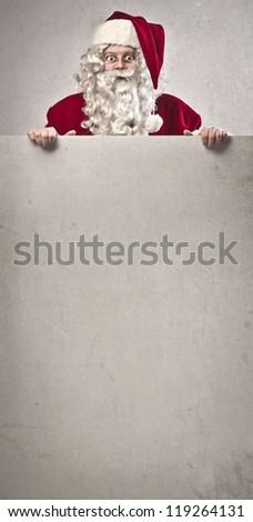 Santa Claus holding a white card board - stock photo