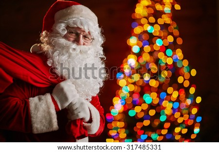 Santa Claus holding carrying sack with gifts for kids - stock photo
