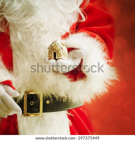 Santa Claus holding Christmas cookies - stock photo