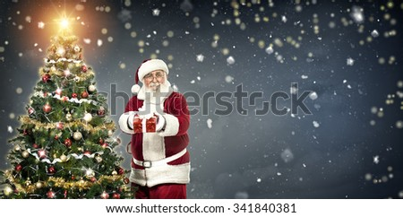 Santa Claus holding gift and standing next Christmas tree on winter background - stock photo