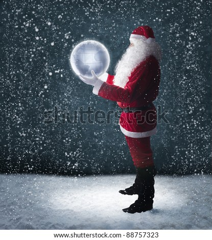 Santa Claus holding glowing planet earth under falling snow - stock photo