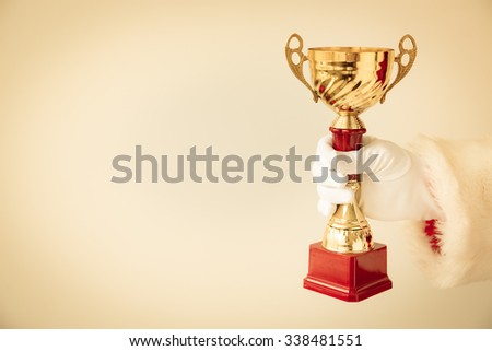 Santa Claus holding gold trophy in hands. Christmas holiday concept - stock photo