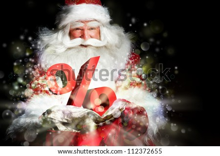 Santa Claus holding his bag and smiling. Lights and sparks are flying from the bag. Discount symbol sign in front of Santa - stock photo