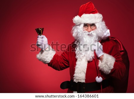 santa claus holding his bag on shoulder and a bell in his right hand on red studio background