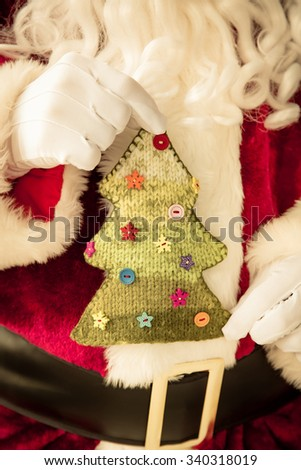 Santa Claus holding holding knitted Christmas tree in hands. Christmas holiday concept - stock photo