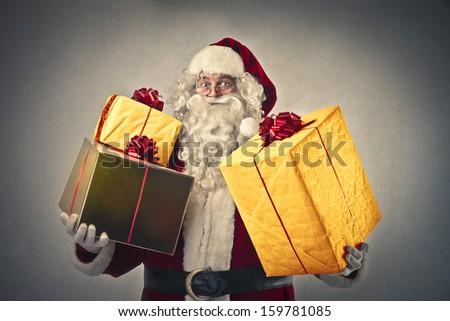 Santa Claus holding many Christmas gifts - stock photo