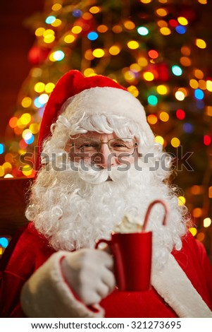 Santa Claus holding red cup with latte on background of sparkling xmas tree - stock photo