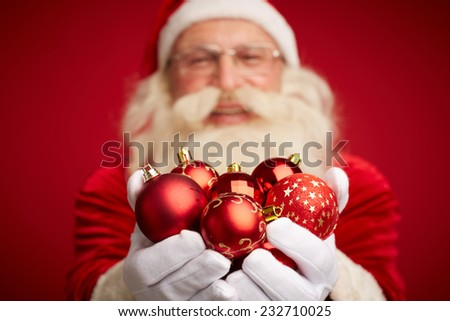 Santa Claus holding red toy balls on palms - stock photo