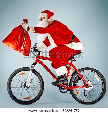 Santa Claus holding sackwith gifts while riding bicycle