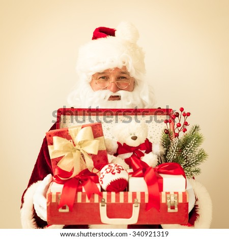 Santa Claus holding suitcase. Christmas holiday concept - stock photo