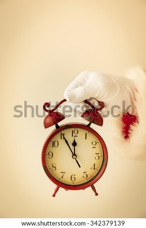 Santa Claus holding vintage alarm clock in hands. Christmas holiday concept - stock photo