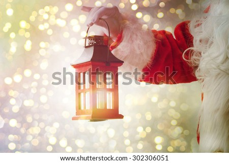 Santa Claus holding  vintage lantern - stock photo