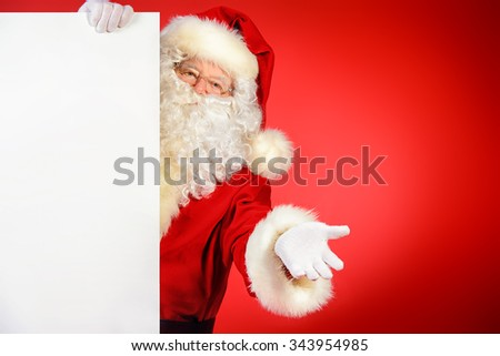 Santa Claus holding white billboard over red background. Copy space. Christmas. - stock photo