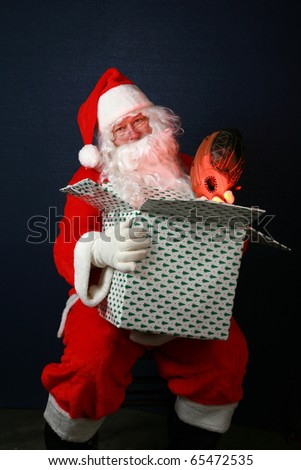 Santa Claus holds a christmas present that he is filling with gifts and the Magic of the Christmas Season. The warm golden glow of christmas magic is lighting up Santas face from inside the box - stock photo