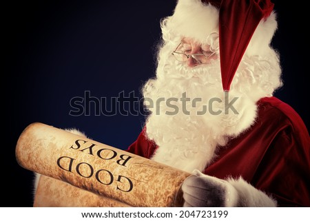 Santa Claus holds an old paper with a list of good boys and girls. Christmas. - stock photo