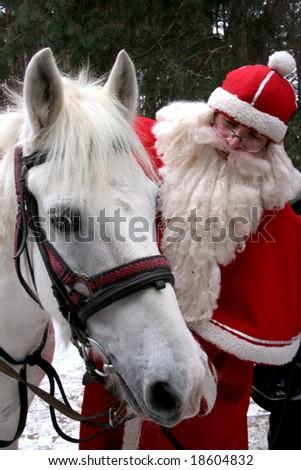 Santa Claus holds white horse - stock photo