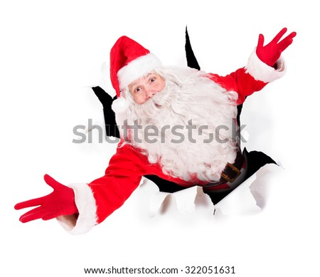 Santa Claus in a hole of paper wall and looking up to camera - stock photo