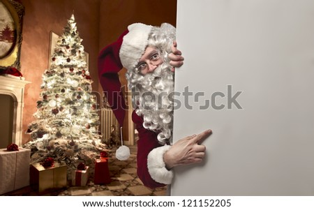 Santa Claus in a house showing something on a white cardboard - stock photo