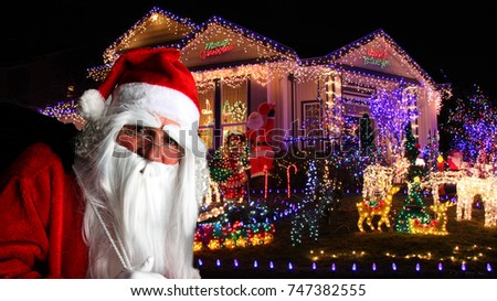 Santa Claus in front of a house decorated with Christmas lights.