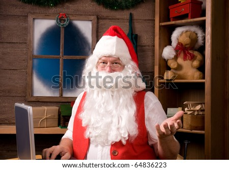 Santa Claus in his workshop with laptop and surrounded by toys and presents.