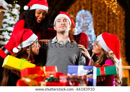 Santa Claus in male and female variants giving Christmas gifts in a shopping mall amid artificial snow covered fir trees and lights