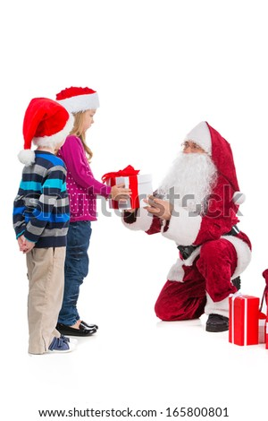 Santa Claus in red costume giving present to beautiful girl . Little polite boy waiting on his turn. Standing together isolated over white background  - stock photo