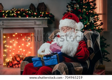 santa claus in traditional red costume holding letter and gift box