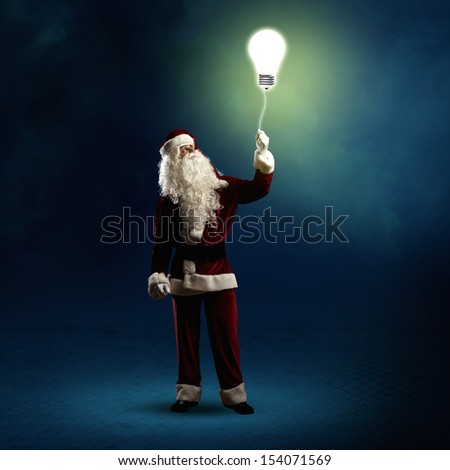 Santa Claus is holding a shining lamp on a string