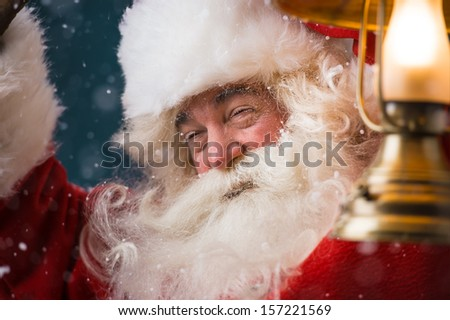 Santa Claus is holding a shining lantern while sneaking to his home outdoors at North Pole  - stock photo