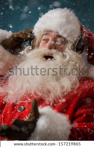 Santa Claus is listening to music in headphones outdoors at North Pole, Having fun while delivering gifts - stock photo
