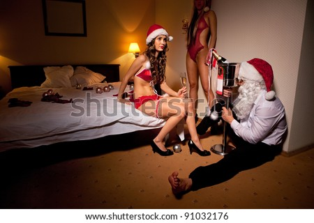 Santa Claus is Passed out Drunk in company of sexy girls - stock photo