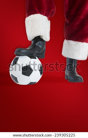 Santa Claus is playing soccer against red background - stock photo