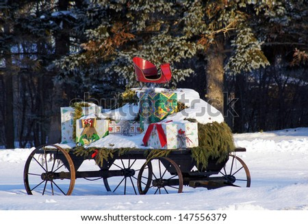 Santa Claus is using a wagon loaded with with pine boughs and Christmas gifts - stock photo