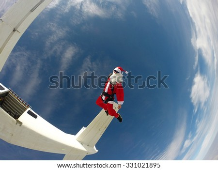 Santa Claus jumping from the plane - Skydiving - stock photo